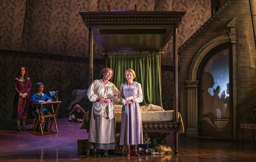 Opera North's production of Britten's The Turn of the Screw  Jennifer Clark as Flora, Tim Gasiorek as Miles, Heather Shipp as Mrs Grose and Sarah Tynan as The Governess. Photo credit: Tristram Kenton
