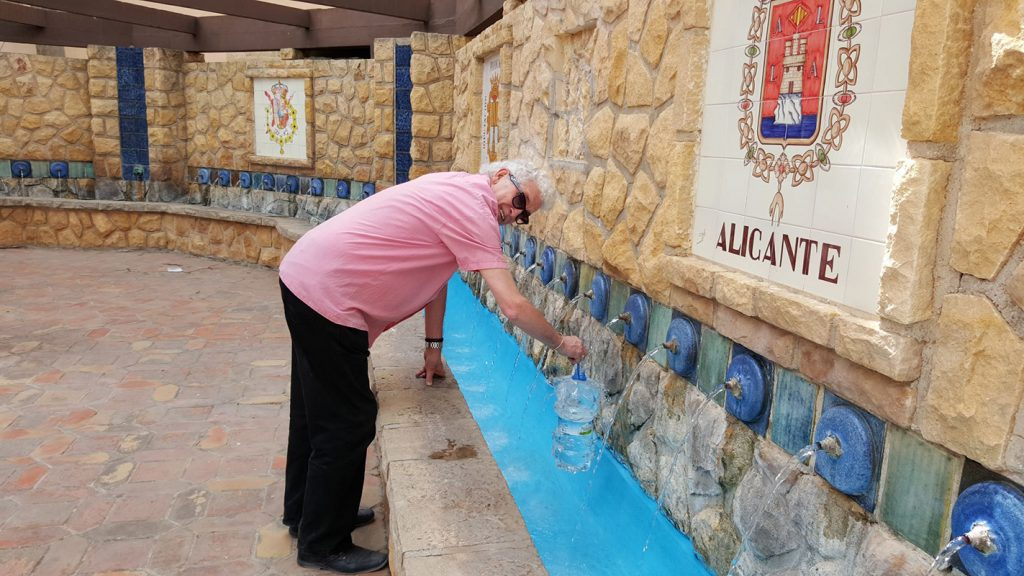 Lorraine's husband,  Bob filling water bottles from the fresh water Chorros Square in Polop Village