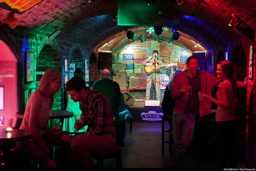 The Cavern Club in Liverpool, the club in Matthew Street where the Beatles music group started their career. The club in a cellar with low arched ceilings. People sitting at tables. Coloured lights and view to the stage. ©Visit Britain/Rod Edwards