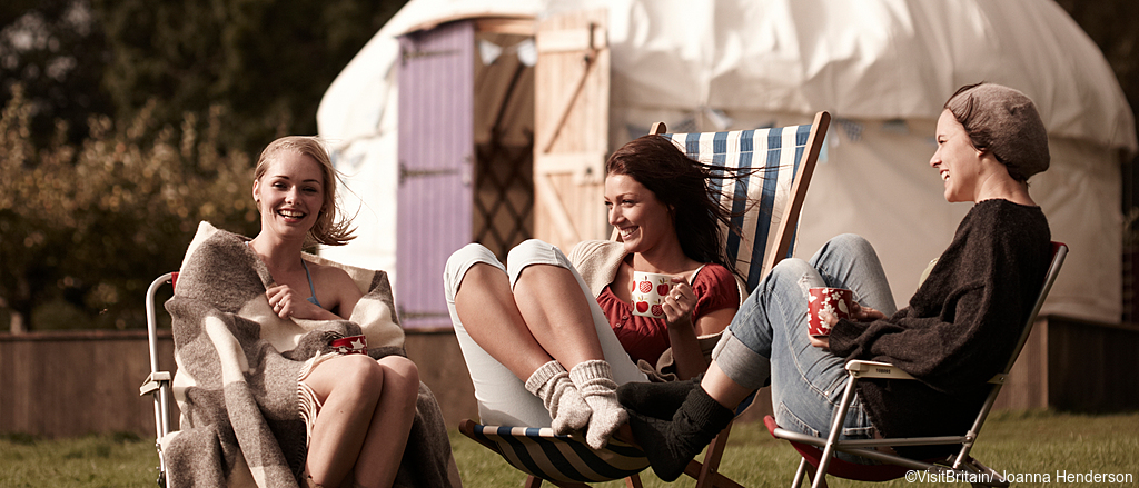 A campsite on a farm in East Sussex. Yurts and teepees in an orchard setting. A group of three young women, friends on a camping holiday.