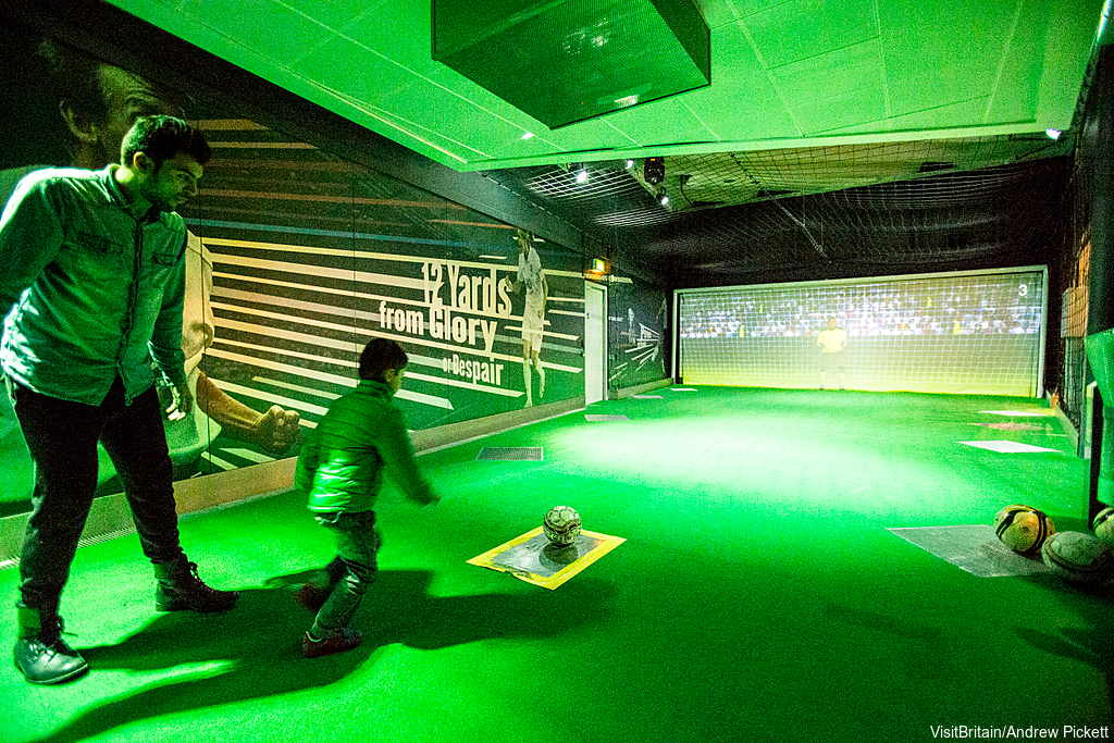 The National Football Museum. Photo: VisitBritain/Andrew Pickett A father and son visiting the museum. Kicking a football and aiming at a goal.