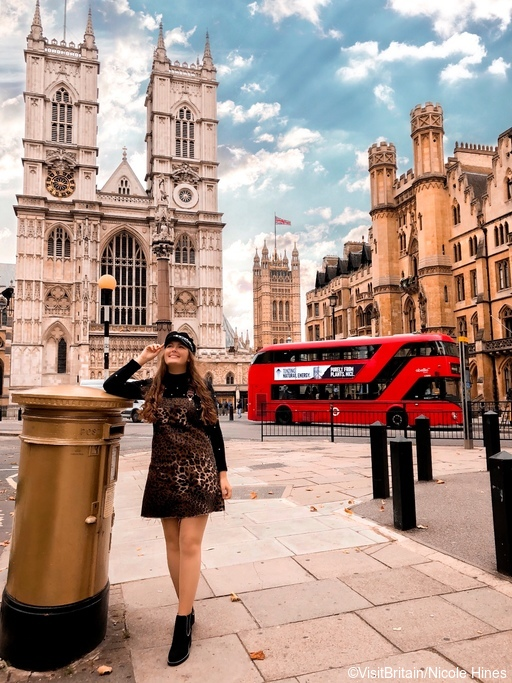 A girl standing by a golden letter box in front of Westminster Abbey with a red bus behind. ©VisitBritain/Nicole Hines