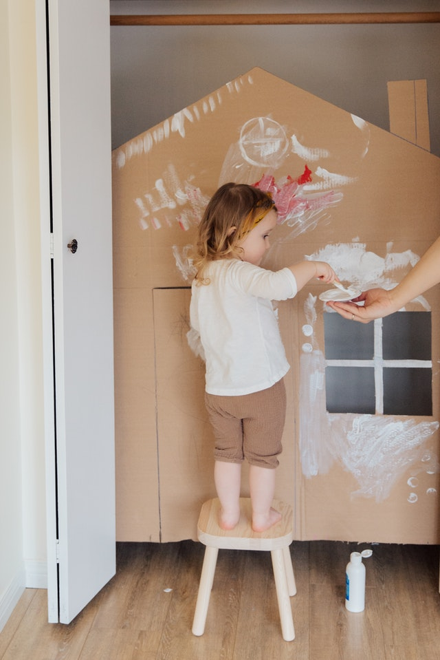 Child painting a Wendy House
